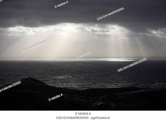 Sun Rays Reflected on Ocean Through Gray Clouds