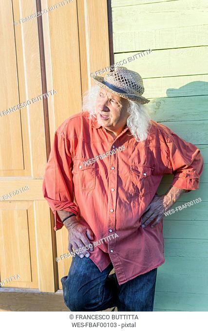 Senior man with long gray hair wearing straw hat looking sideways