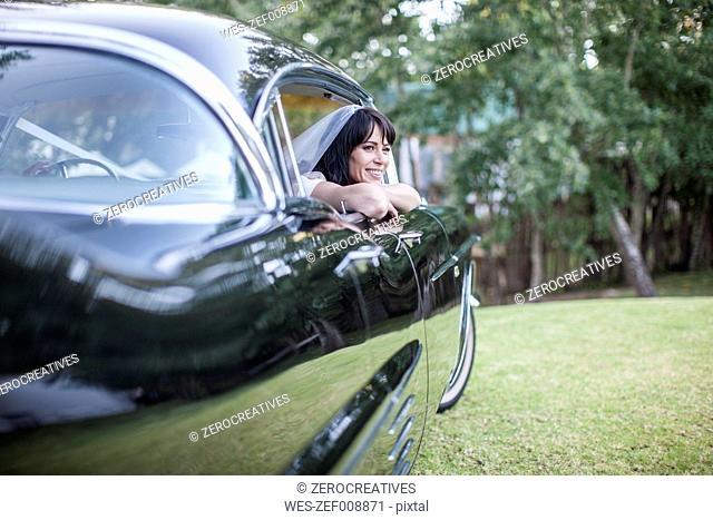 Smiling bride sitting in vintage car