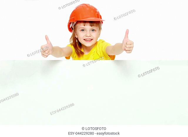 A nice little girl in a construction helmet and a yellow T-shirt peeped out from behind a white advertising banner.She shows the gesture OK