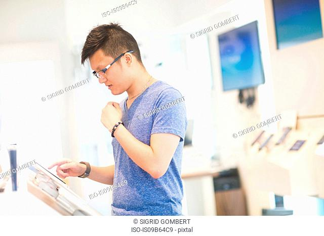 Man using digital tablet in technology shop