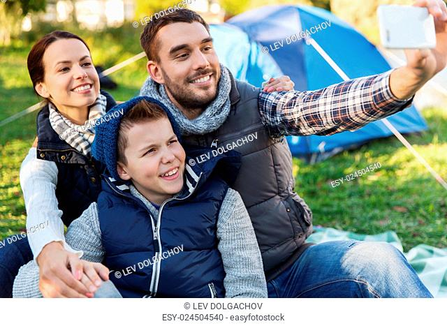 camping, hike, technology and people concept - happy family with smartphone taking selfie at campsite