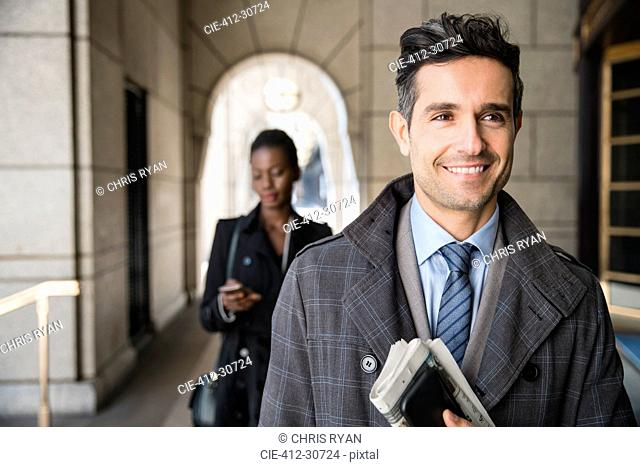 Smiling corporate businessman carrying newspaper and cell phone in cloister