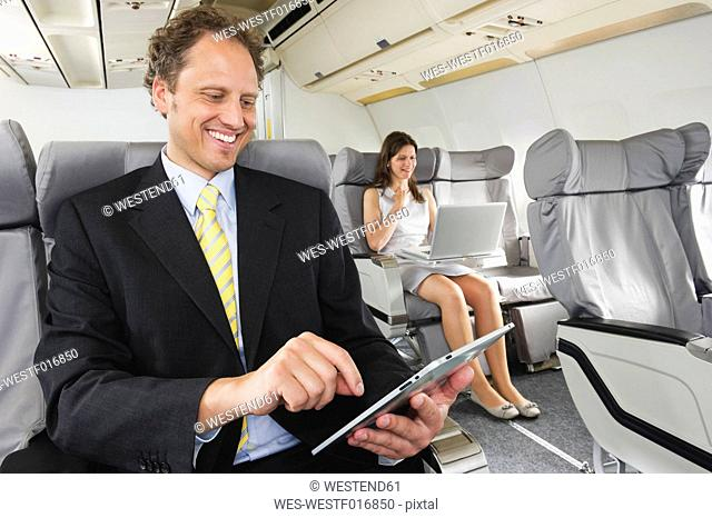 Germany, Bavaria, Munich, Business people working on ipad and laptop in business class airplane cabin, smiling