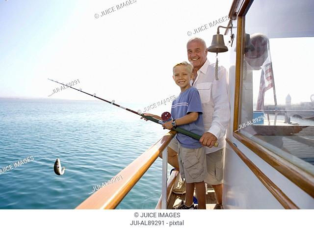 Grandfather and grandson fishing on boat