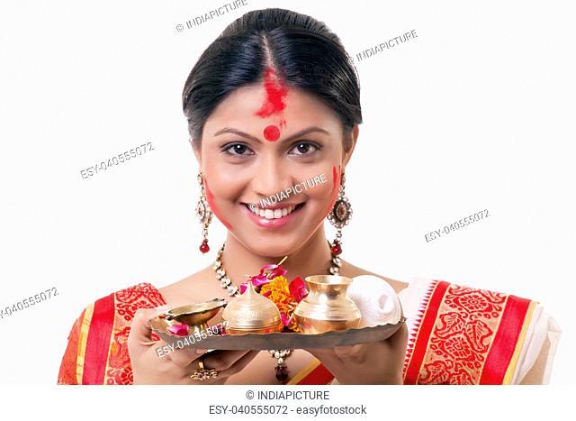 Portrait of a Bengali woman holding a puja thali