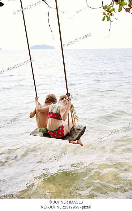 Boy and girl on swing at sea