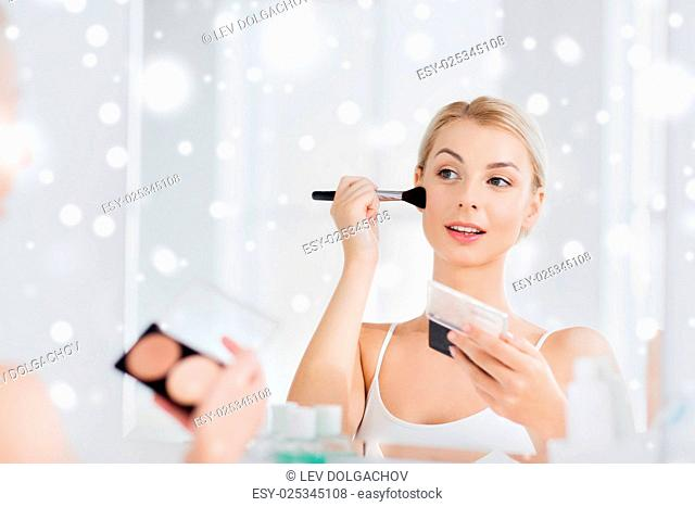 beauty, make up, cosmetics, morning and people concept - young woman with makeup brush and contouring and highlighting palette looking to mirror at home...