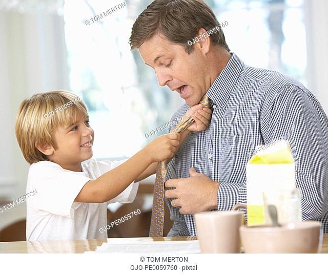 Young boy tightening man's necktie in kitchen