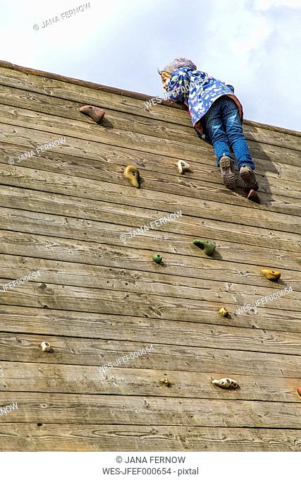 Little girl moving on climbing wall