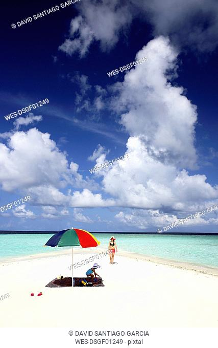 Maldives, Gulhi, mother and daughter on sandbank in shallow water