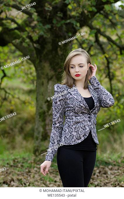 Sad young woman standing in the countryside
