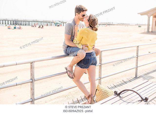 Couple on railings by beach kissing, Coney island, Brooklyn, New York, USA