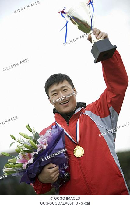 Male athlete wearing a gold medal and waving trophy