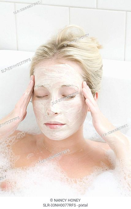 Woman wearing mask in bubble bath