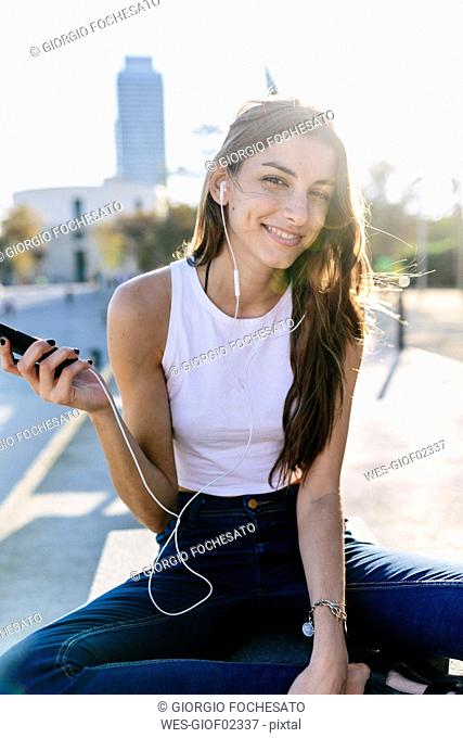 Spain, Barcelona, portrait of smiling young woman relaxing at sunset listening music with earphones
