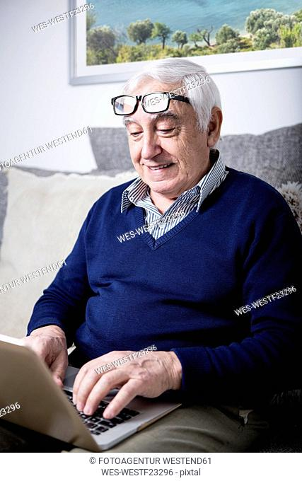 Senior man sitting on couch, using laptop