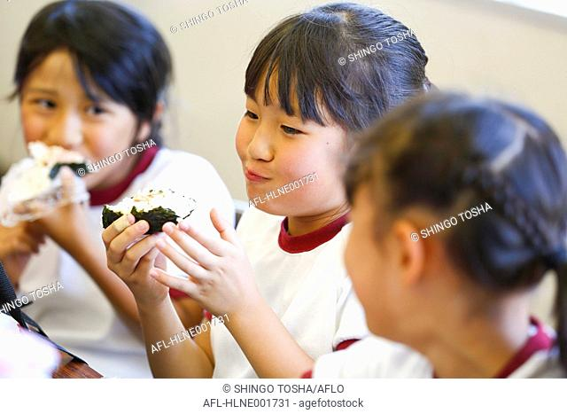 Japanese elementary school kids eating in the classroom