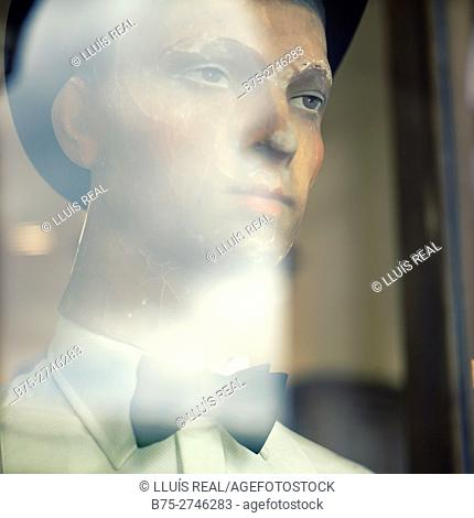 Old mannequin in shop window with hat and bow tie, reflections on glass