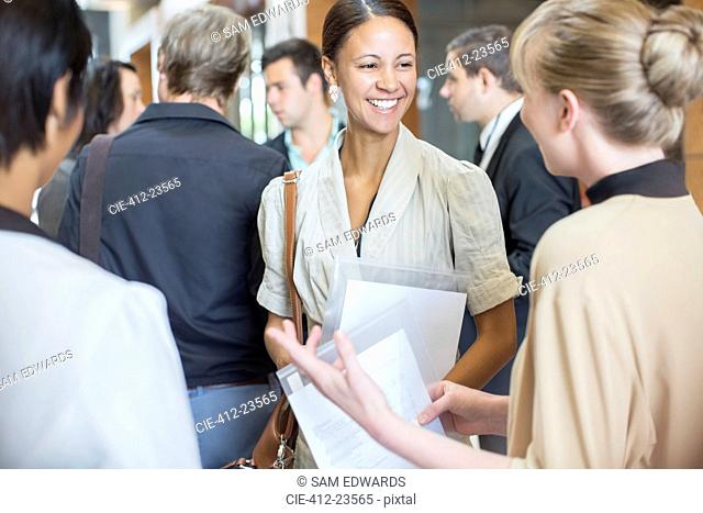 Portrait of two smiling women holding files and talking, standing in crowded lobby