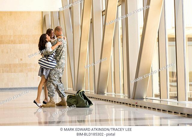 Returning soldier greeting family in airport