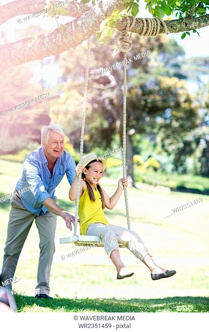 Grandfather pushing his granddaughter on swing