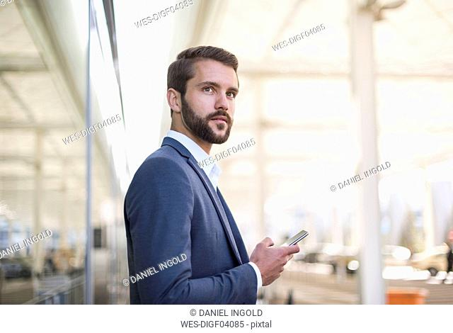 Young businessman holding cell phone looking sideways