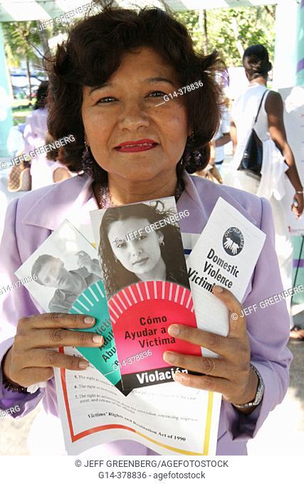 Woman displays information brochures. Domestic Violence March event, Safespace Foundation. Ocean Drive. Lummus Park. South Beach. Miami Beach. Florida