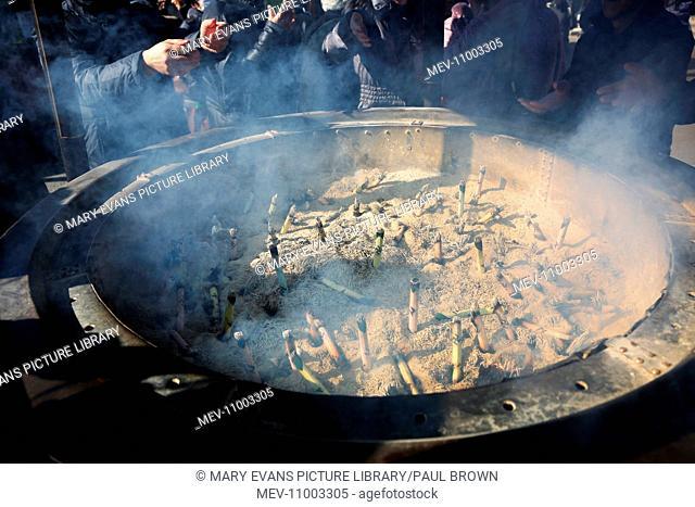 People burning incense at the Shinto Shrine at Senso-Ji Bhuddist Temple in Asakusa in Tokyo, Japan