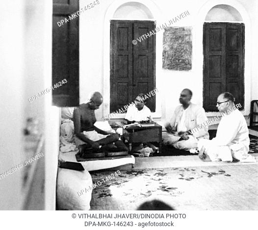 Mahatma Gandhi spinning and talking with Dr Shyam Prasad Mukherjee and others at New Delhi , 1946 , India NO MR
