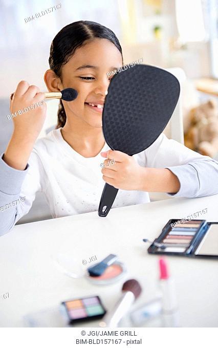 Mixed race girl applying makeup with brush