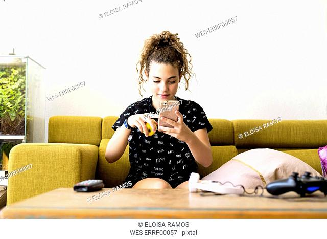 Portrait of girl sitting on the couch at home using smartphone