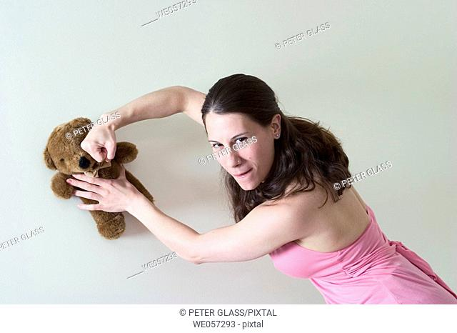 Young woman pretending to punch a stuffed animal
