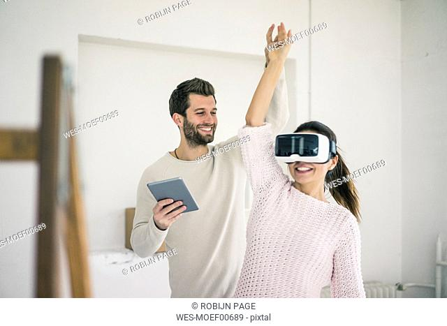 Man lifting woman's arm wearing VR glasses in new home