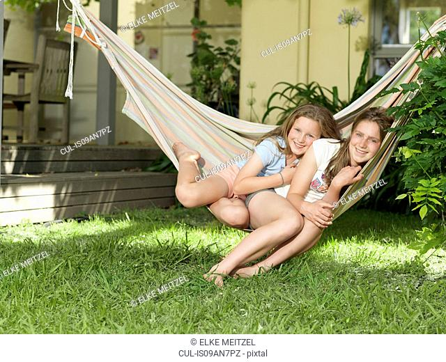 Two sisters sitting on hammock together