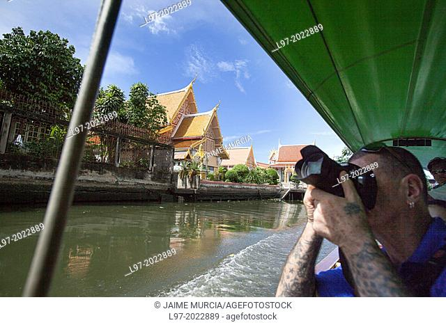 A tourist photographs temples from a longboat on one of Bangkoks many canals, Thailand