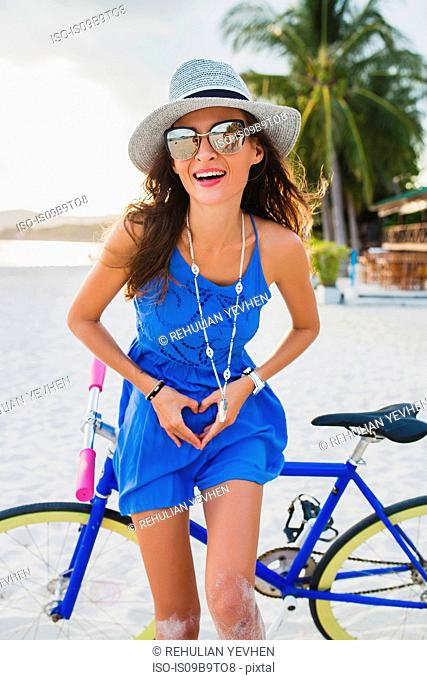 Portrait of young woman with bicycle making heart shape with hands on sandy beach, Krabi, Thailand