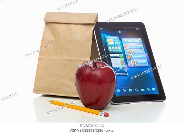 Paper bag, apple, tablet and pencil on white background