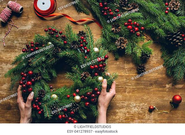 top view of female hands holding Christmas wreath on wooden tabletop