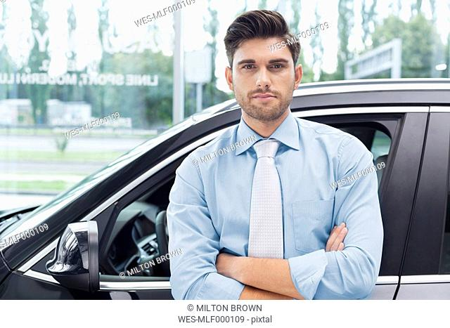 At the car dealer, Portrait of confident salesman