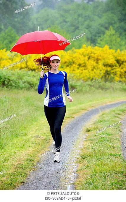 Teenage girl running with umbrella on dirt track, Bainbridge Island, Washington, USA