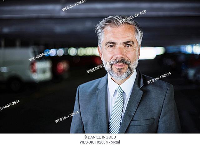 Portrait of confident businessman in parking garage