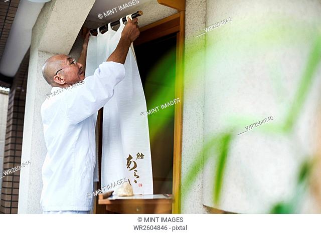 A chef in a small commercial kitchen, an itamae or master chef drawing a curtain across a door