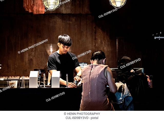Male barista serving customer at counter in independent coffee roaster and cafe, Bangkok