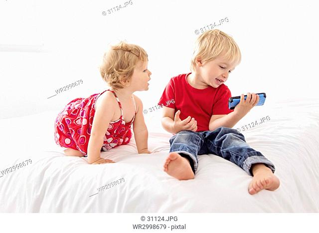 Young girl wearing red dress and boy holding blue smart phone sitting on a bed