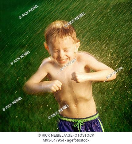 Young boy reacting to being sparyed with water hose