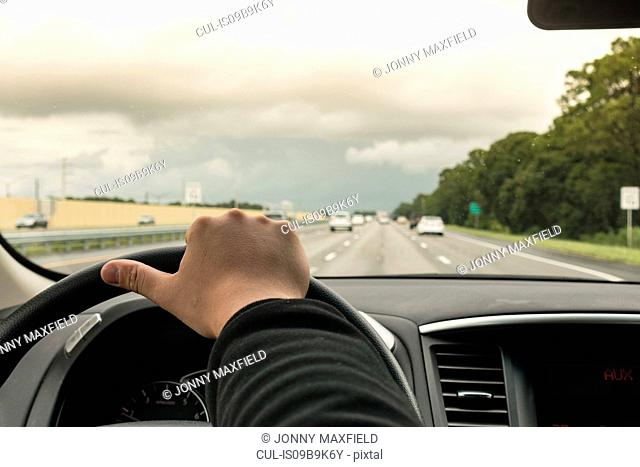 Man driving car on highway, Florida, USA, close up of hand and steering wheel