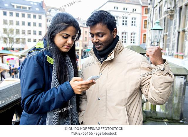 Aachen, Germany. Young, Indian couple of university exchange students navigating their new city using a smartphone map application