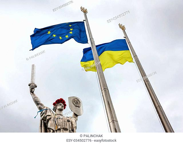 """KIEV, UKRAINE - May. 08, 2015: Flags of the European Union and Ukraine against monumental statue of the """"""""Mother Motherland"""""""" devoted the Great Patriotic War"""