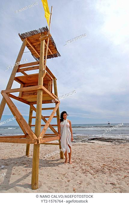 Brunette young woman posing on the beach, standing by a lifeguard post